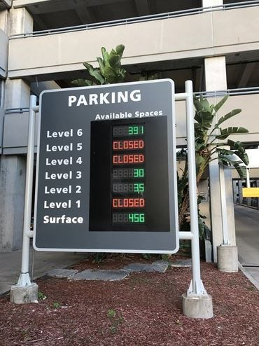 Digital side by entrance to parking garage informing drivers how many spaces there are per level.